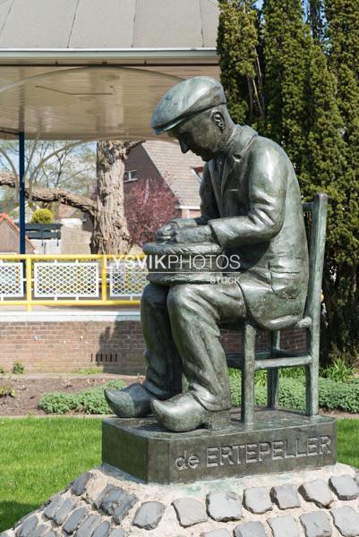De erwtepeller, bronzen beeld van zittende man