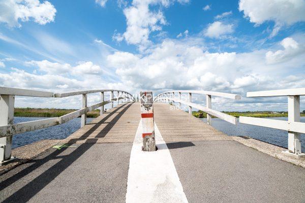 Houten voetgangers en fietsersbrug over het riviertje de Groote of Achterwaterschap in de polders bij Streefkerk in de Molenwaard