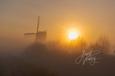 Broekmolen in mist bij zonsopkomst