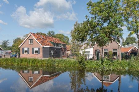 Woningen gespiegeld in riviertje de Graafstroom