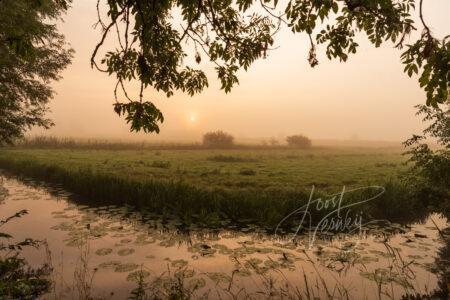 Doorkijkje met zonsopkomst in mistig polderlandschap